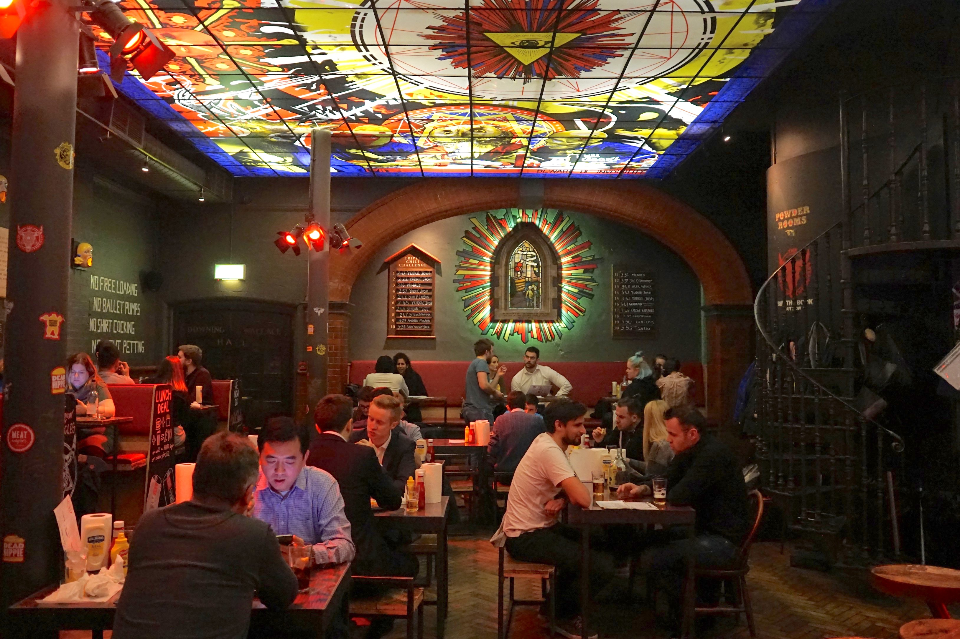 The interiors of MEATMission in Shoreditch with people inside and stained windows.